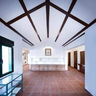 Foto di un soggiorno stile rurale aperto con libreria, pareti bianche, pavimento con piastrelle in ceramica e pavimento rosso