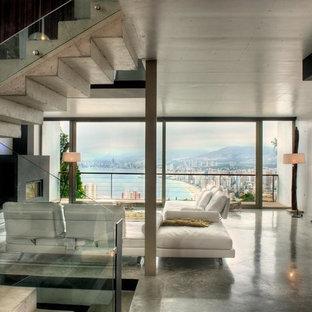 Imagen de salón abierto, actual, con suelo de cemento, chimenea tradicional, marco de chimenea de yeso y televisor colgado en la pared