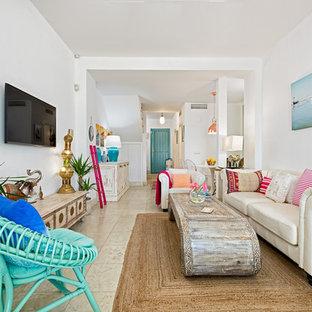Ejemplo de salón para visitas abierto, tropical, grande, sin chimenea, con paredes blancas, suelo de mármol y televisor colgado en la pared