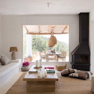 Imagen de salón mediterráneo, sin televisor, con paredes blancas, chimenea de esquina y marco de chimenea de metal