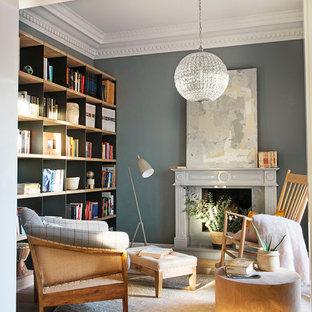 Modelo de biblioteca en casa abierta, clásica renovada, de tamaño medio, sin televisor, con paredes grises, suelo de madera clara, suelo marrón y chimenea tradicional