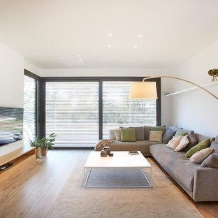 Imagen de salón para visitas cerrado, moderno, con paredes blancas, suelo de madera en tonos medios, chimenea lineal, televisor colgado en la pared y suelo beige