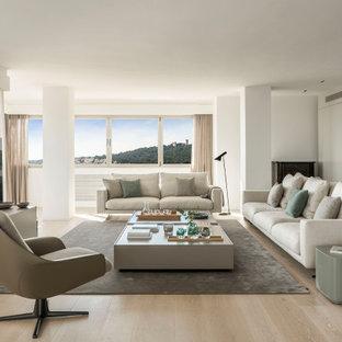 Ejemplo de salón abierto, contemporáneo, con paredes blancas, suelo de madera clara, televisor independiente y suelo beige