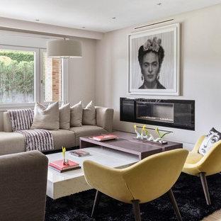 Diseño de salón contemporáneo con paredes beige, suelo de madera clara, chimenea lineal y suelo beige