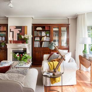 Imagen de salón para visitas clásico renovado con paredes grises, suelo de madera en tonos medios, chimenea tradicional y suelo marrón