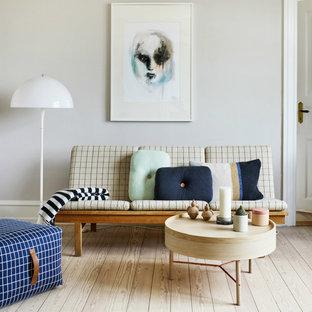 Diseño de salón abierto, nórdico, pequeño, sin chimenea y televisor, con suelo de madera clara y paredes grises