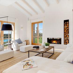 マヨルカ島の地中海スタイルのおしゃれなLDK (白い壁、標準型暖炉、石材の暖炉まわり、テレビなし、白い床) の写真