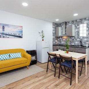 Ejemplo de salón abierto, contemporáneo, pequeño, con paredes blancas, suelo de madera en tonos medios, televisor colgado en la pared y suelo marrón
