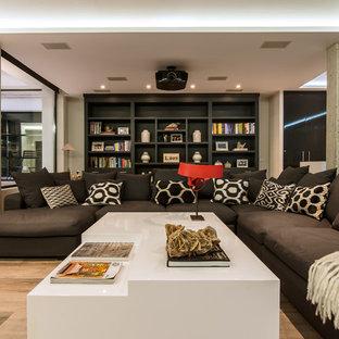 Diseño de salón para visitas abierto, contemporáneo, grande, con paredes multicolor, suelo de madera en tonos medios y pared multimedia