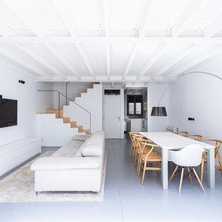 Imagen de salón abierto, contemporáneo, sin chimenea, con paredes blancas, televisor colgado en la pared y suelo gris