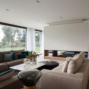 Foto de salón abierto, actual, con paredes blancas, chimenea de doble cara y suelo beige
