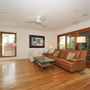 Immagine di un grande soggiorno contemporaneo stile loft con libreria, pareti bianche, pavimento in compensato, nessun camino e parete attrezzata