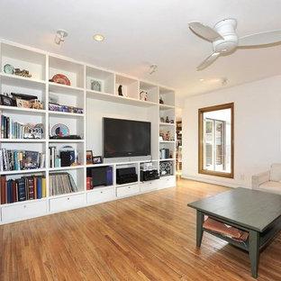 Foto di un grande soggiorno contemporaneo stile loft con libreria, pareti bianche, pavimento in compensato, nessun camino e parete attrezzata