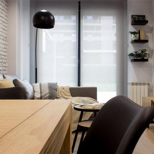 Diseño de salón cerrado y ladrillo, escandinavo, pequeño, ladrillo, con paredes grises, suelo de madera clara, televisor colgado en la pared y ladrillo