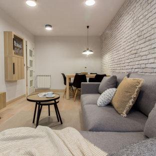 Foto de salón cerrado y ladrillo, industrial, pequeño, ladrillo, con paredes grises, suelo de madera clara, televisor colgado en la pared y ladrillo