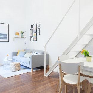 Foto di un soggiorno nordico di medie dimensioni e stile loft con pareti bianche, pavimento in laminato, stufa a legna, nessuna TV e pavimento marrone