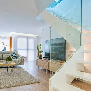 Modelo de salón abierto, contemporáneo, con paredes blancas, suelo de madera clara, televisor independiente y suelo beige