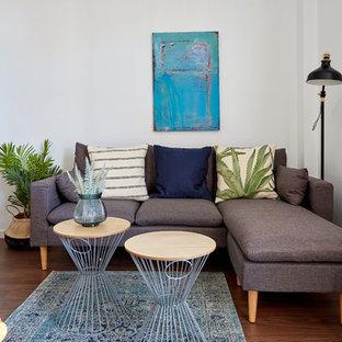 Ejemplo de salón para visitas abierto, actual, de tamaño medio, con paredes blancas, suelo de madera oscura y suelo marrón