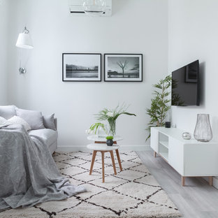 Modelo de salón abierto, escandinavo, pequeño, sin chimenea, con paredes blancas, televisor colgado en la pared, suelo gris y suelo laminado