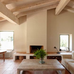 Imagen de salón para visitas abierto, de estilo de casa de campo, grande, sin televisor, con paredes amarillas, suelo de baldosas de terracota y chimenea tradicional