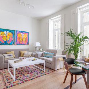 Modelo de salón abierto, tradicional renovado, con paredes blancas, suelo de madera clara y suelo beige
