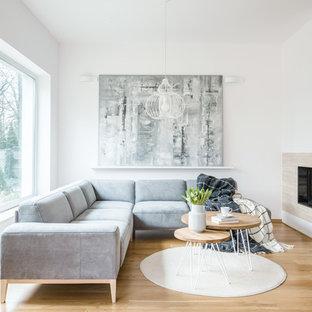Modelo de salón abierto, contemporáneo, con paredes blancas, suelo de madera en tonos medios, chimenea de esquina y suelo marrón
