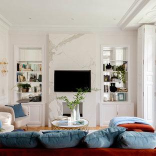 Foto de salón abierto, tradicional renovado, grande, con paredes blancas, suelo de madera en tonos medios, televisor colgado en la pared, suelo marrón, chimenea tradicional y marco de chimenea de piedra