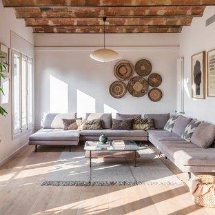 This is an example of a mediterranean formal open concept living room in Barcelona with light hardwood floors, no fireplace, no tv and beige floor.