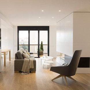 Imagen de salón abierto, escandinavo, de tamaño medio, con paredes blancas, suelo de madera en tonos medios, chimenea de doble cara, marco de chimenea de madera, suelo marrón y televisor retractable