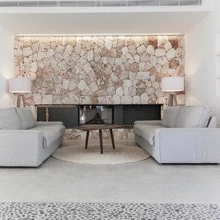 マヨルカ島の中サイズの地中海スタイルのおしゃれな独立型リビング (フォーマル、白い壁、コンクリートの床、横長型暖炉、石材の暖炉まわり) の写真