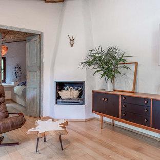 Imagen de salón mediterráneo con paredes blancas, suelo de madera clara, chimenea de esquina y marco de chimenea de yeso