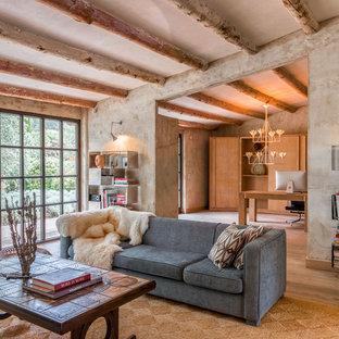 Ejemplo de biblioteca en casa mediterránea con paredes grises y suelo de madera clara