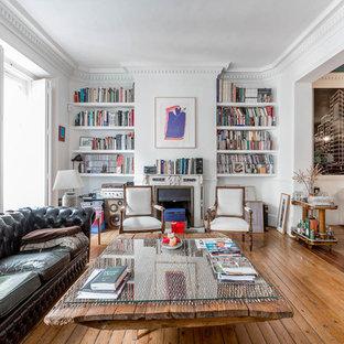 Imagen de biblioteca en casa abierta, bohemia, grande, con chimenea tradicional, paredes blancas, suelo de madera en tonos medios y suelo marrón