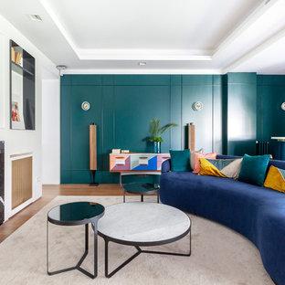 Foto de salón con barra de bar contemporáneo con paredes verdes, suelo de madera en tonos medios, chimenea lineal y marco de chimenea de piedra