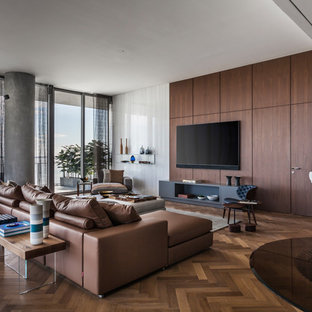 Photo of a contemporary living room in Miami with brown walls, medium hardwood flooring, a wall mounted tv and brown floors.