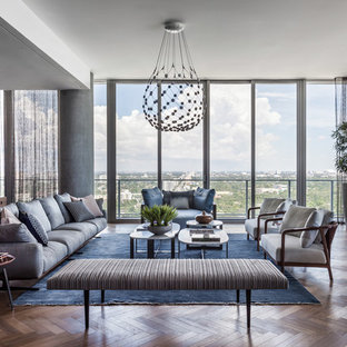 Example of a trendy medium tone wood floor and brown floor living room design in Miami with blue walls