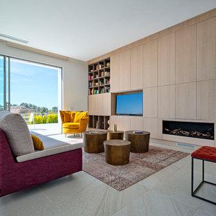 Imagen de salón abierto, actual, grande, con paredes blancas, pared multimedia, suelo blanco y chimenea lineal