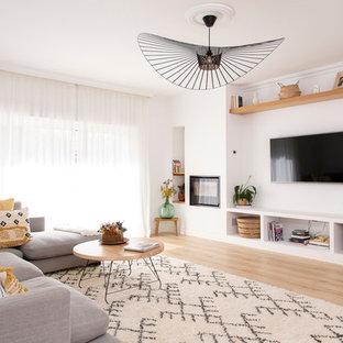 Imagen de salón abierto, contemporáneo, grande, con paredes blancas, suelo de madera clara, chimenea tradicional, marco de chimenea de metal, televisor colgado en la pared y suelo beige