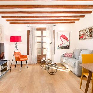 Diseño de salón abierto, contemporáneo, de tamaño medio, con paredes blancas, suelo de madera en tonos medios, televisor independiente y suelo marrón