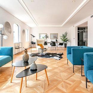 Modelo de salón abierto, contemporáneo, grande, con suelo de madera en tonos medios, paredes blancas y suelo beige