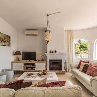 Ejemplo de salón para visitas cerrado, mediterráneo, con paredes blancas, chimenea tradicional, marco de chimenea de ladrillo, televisor independiente y suelo beige