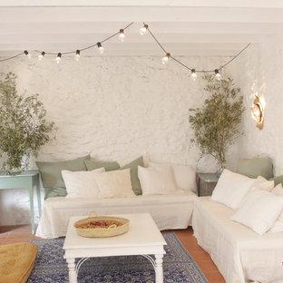 Exemple d'un salon méditerranéen avec un mur blanc, un sol en carreau de terre cuite et un sol rouge.