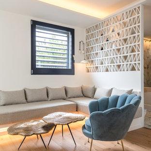 Diseño de salón contemporáneo con paredes blancas, suelo de madera en tonos medios y suelo marrón