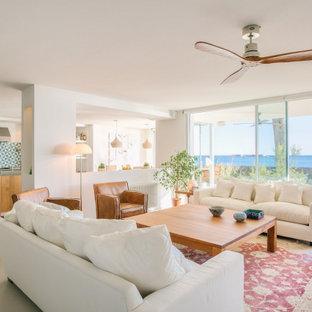 Imagen de salón abierto, contemporáneo, con paredes blancas, suelo de cemento y suelo gris