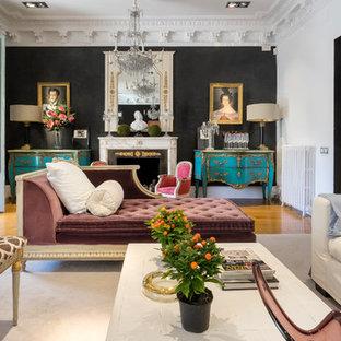 Diseño de salón para visitas abierto, bohemio, con paredes negras, chimenea tradicional, suelo de madera en tonos medios y suelo beige