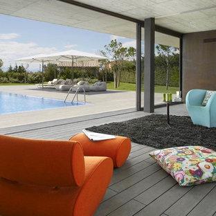 Immagine di un grande soggiorno contemporaneo aperto con sala formale, pareti marroni, pavimento in legno verniciato, nessun camino e nessuna TV