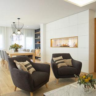 Modelo de salón abierto, contemporáneo, grande, con paredes blancas, suelo de madera en tonos medios y suelo beige