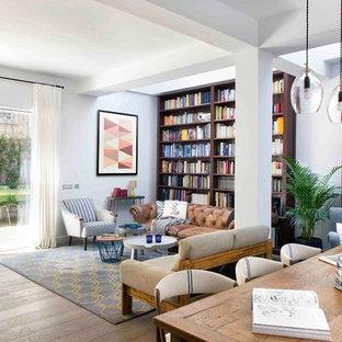 Ejemplo de biblioteca en casa abierta, actual, extra grande, con paredes blancas, suelo de madera clara y suelo beige