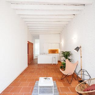 Foto de salón abierto, mediterráneo, con paredes blancas, suelo de baldosas de terracota y suelo naranja