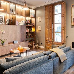 Ejemplo de biblioteca en casa clásica renovada, de tamaño medio, con paredes grises, suelo de madera en tonos medios, televisor retractable y suelo marrón